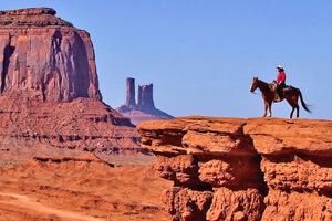 Die Top Sehenswürdigkeit im Südwesten der USA. Mann auf Pfer vor dem Monument Valley