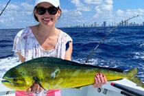 Frau hängt einen Fisch beim Hochseeangeln