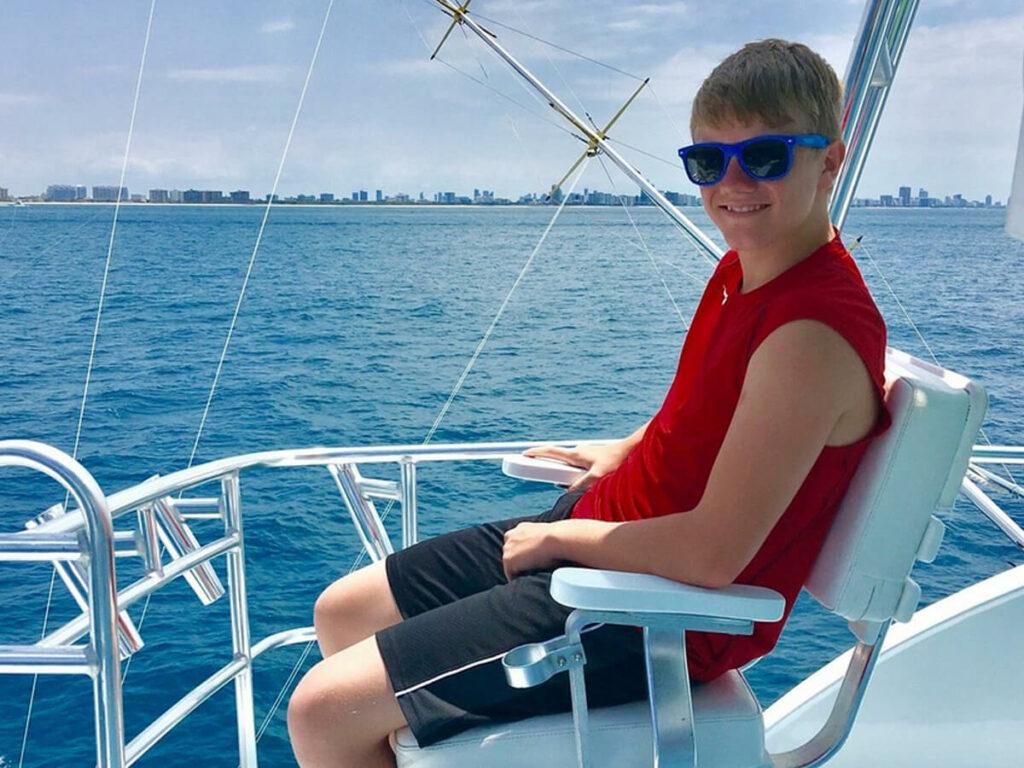 Junde auf einem Boot und angelt