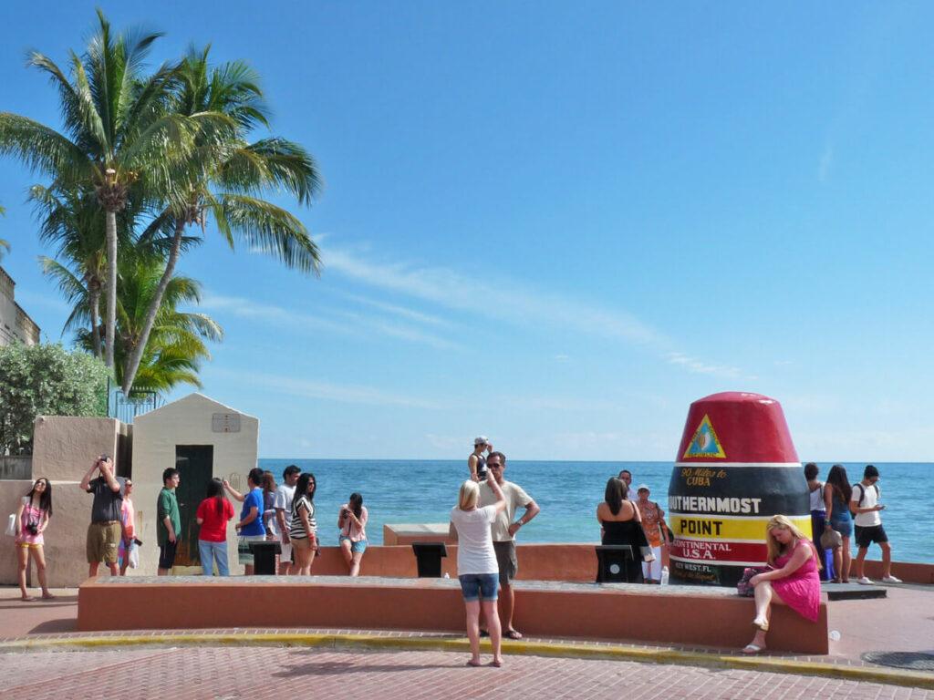 Touristen stehen schlange am Southernmost Point für ein Foto
