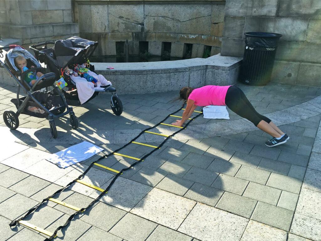 Frau mit Kinderwagen mach ein Workout an den Rocky Steps