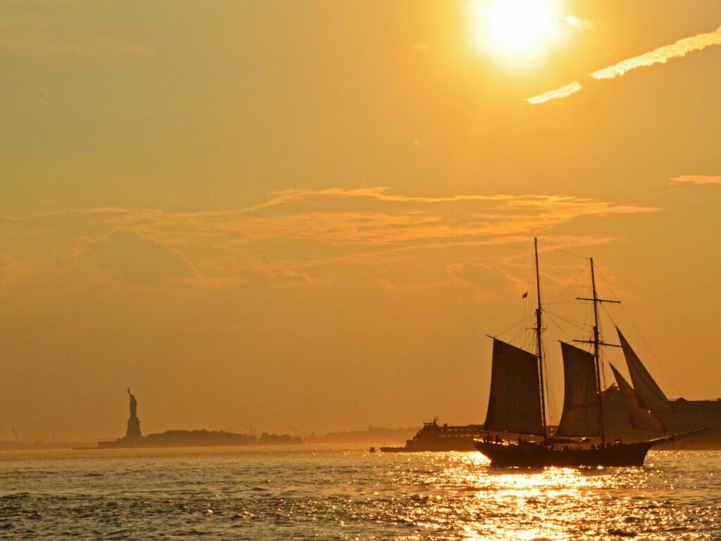 Segelboot beim Sonnenuntergang an der Freiheitsstatue